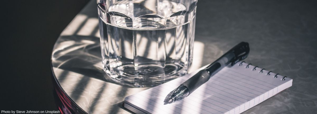 glass of water on a table with a notepad and pen