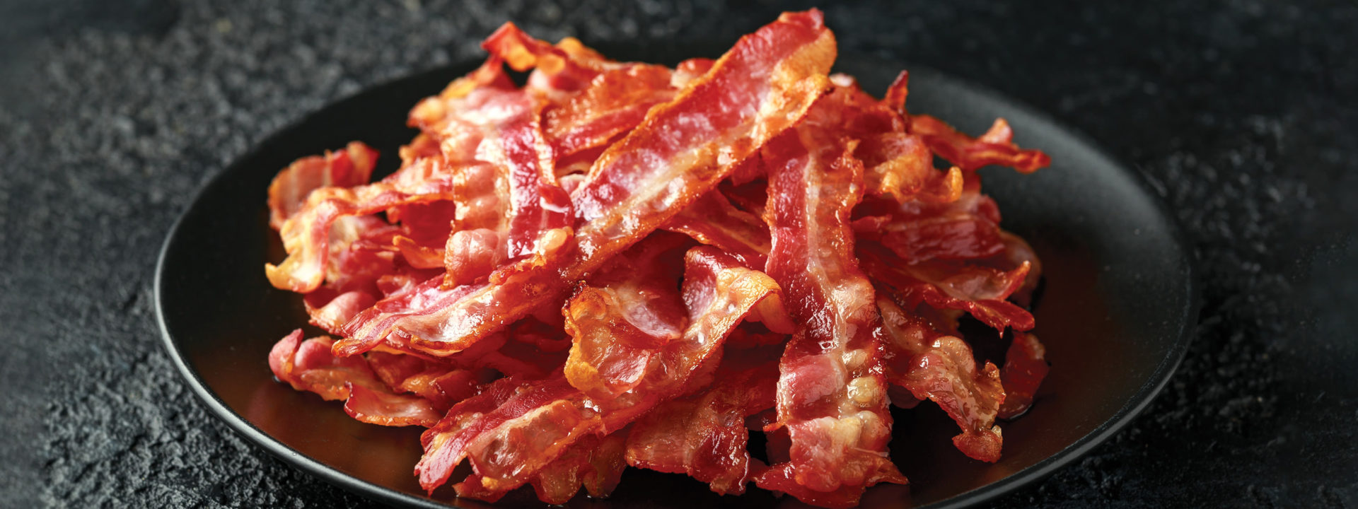 Stack of cooked bacon on a black plate on a black concrete countertop