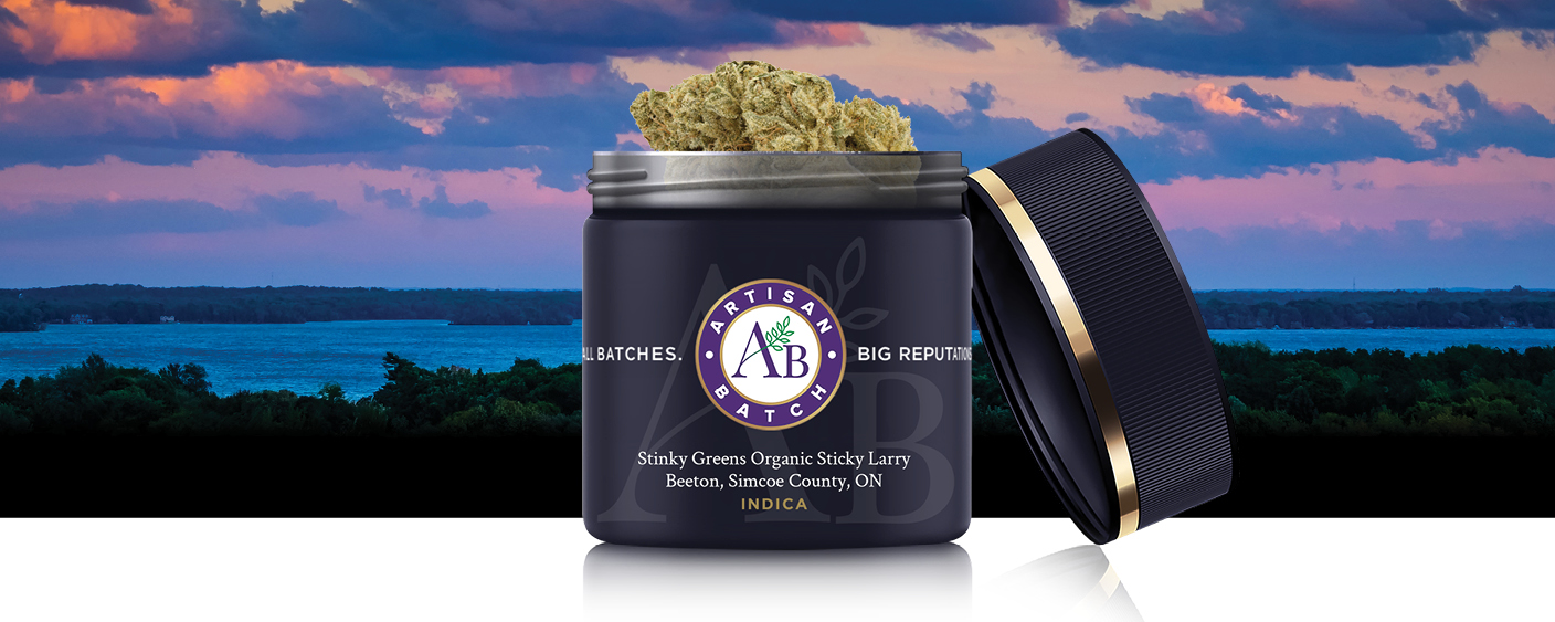Blue jar of Stinky Greens Organic Sticky Larry with lid open and bud sticking out, Simcoe County waterway in background with pink and purple sunset