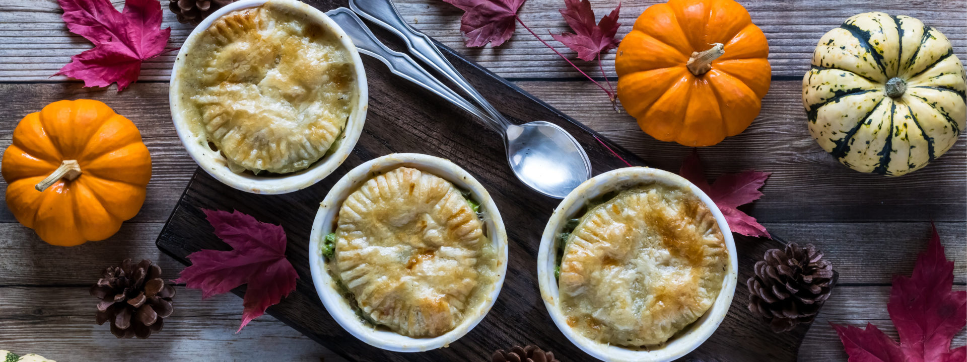 Three small turkey pot pies on a wooden plant serving board, seen from above with two spoons, pinecones, pumpkins and leaves around them