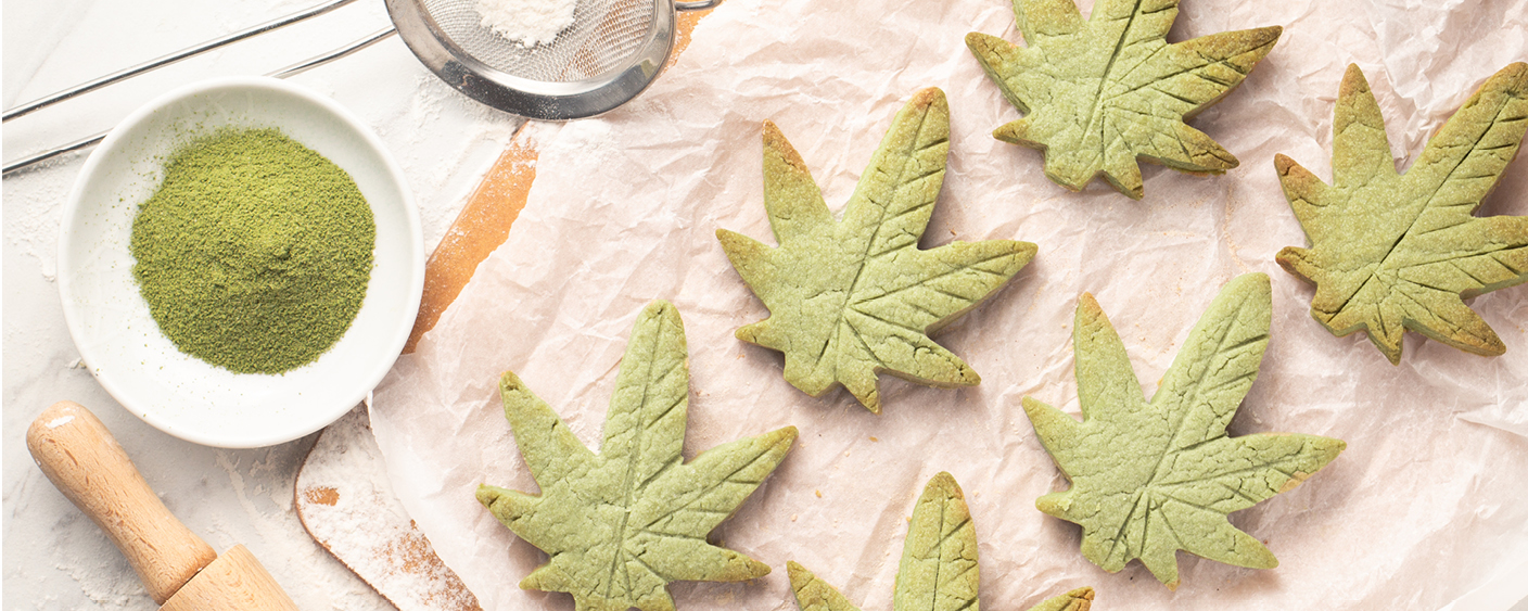 cannabis leaf shaped sugar cookies on parchment paper with flour and rolling pin